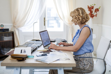 Pretty elegant woman furniture designer working at her office.