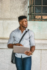 African American College Student studying in New York. Wearing gray shirt, jeans, carrying shoulder leather bag, a black man standing against wall on street, reading, working on laptop computer..