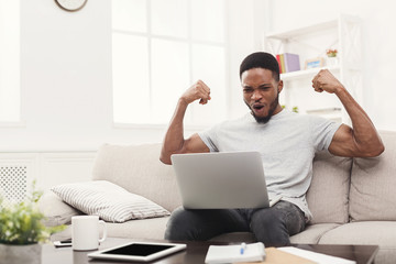 Young black man with arms raised with laptop celebrating success