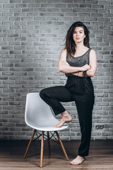 Beautiful business woman standing next to a chair and thinking about something