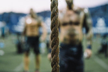 Close-up of rope in gym with shirtless men standing in background