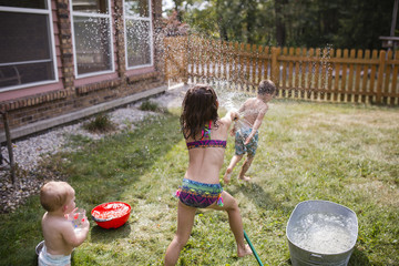 Baby girl looking at sister spraying water on shirtless brother through hose