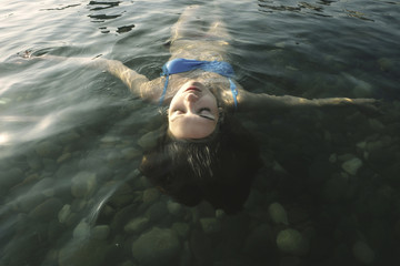 High angle view of carefree woman with eyes closed floating on water in river