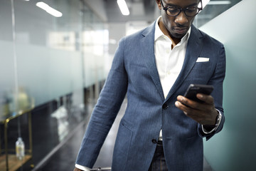 Serious businessman using smart phone while standing in office