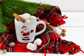 A cup of hot winter drink with marshmallow and cinnamon. New Year's background.