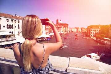 beautiful girl taking a photo on a modern mobile phone (smartphone) canal in Venice, Italy standing on a bridge