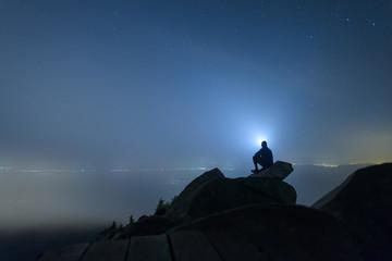 Silhouette of man sitting on mountain peak against sky
