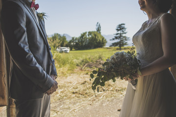 Midsection of bride and groom standing face to face against field and sky