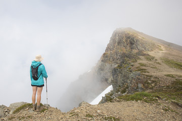High angle view of female hiker with backpack standing at Cheam Peak during foggy weather