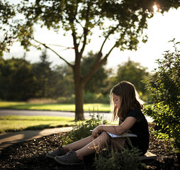 Side view of girl writing on book while sitting at park