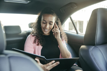 Businesswoman looking at file while talking on smart phone in car