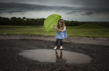 Girl holding umbrella while walking into puddle on road against stormy clouds