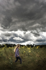 Carefree girl walking amidst plants on field against stormy clouds