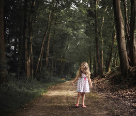 Girl standing on dirt road amidst forest