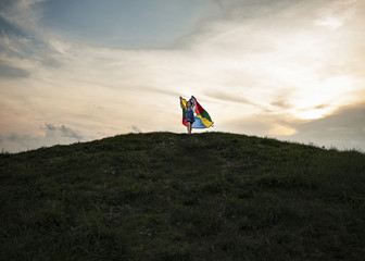 Low angle view of playful girl holding multi colored textile while running on hill against cloudy sky