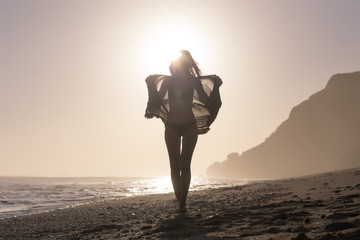 Full length of woman wearing bikini while holding textile against clear sky at beach during sunset