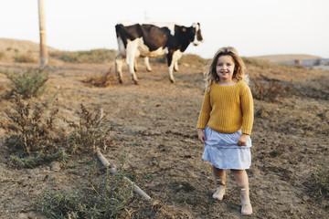 Full length portrait of girl standing on field against cow