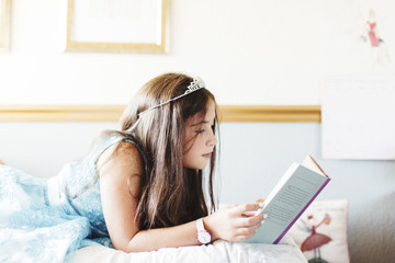 Side view of girl wearing tiara while reading book on bed