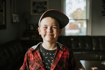 Portrait of happy boy wearing cap at home