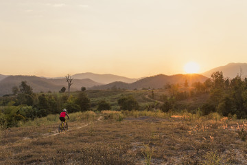 View of man mountain biking on field against sky during sunset