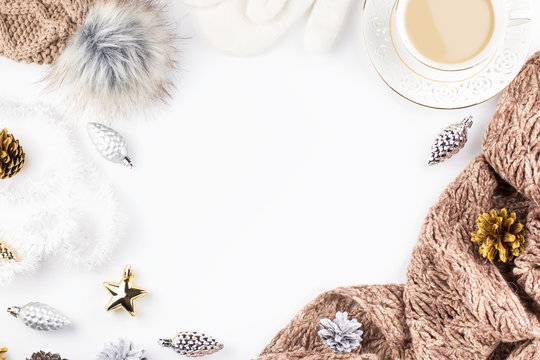 Christmas concept flat lay. Warm, cozy winter clothing, hot drink and Christmas decorations frame on white background