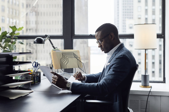 Serious businessman working while sitting against window in office