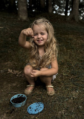 Girl holding insect while crouching in forest