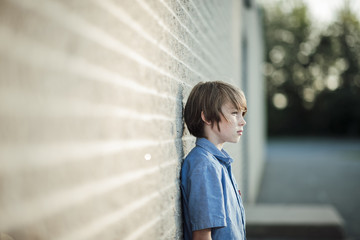 bd14189e208 Thoughtful boy looking away while leaning against wall