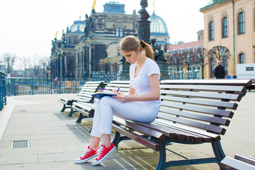The girl in The Dresden sitting on the bench and writes in diary and laptop