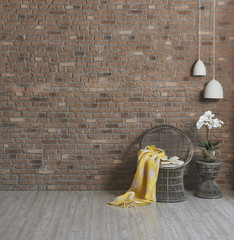 wicker armchair and natural wall paper with vase of flower