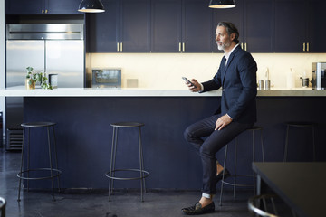 Full length of businessman looking away while holding smart phone at kitchen counter in creative office