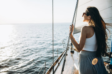A beautiful girl with long hair in the glasses stands on a yacht and admires the sunset
