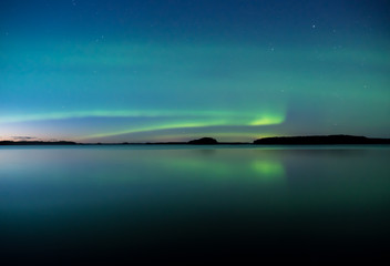Northern lights dancing over calm lake in Farnebofjarden national park in Sweden