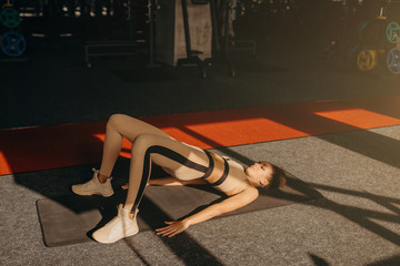 Athletic girl in rose sportswear does stretching exercise on the track indoors. She holds her feet on the toes and raises her pelvis while relies on the hands and shoulders.