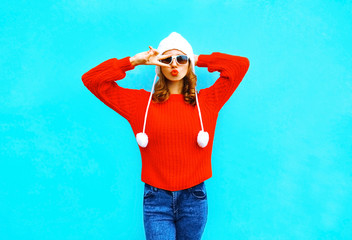 Fashion woman in red knitted sweater, hat on a blue background in the city