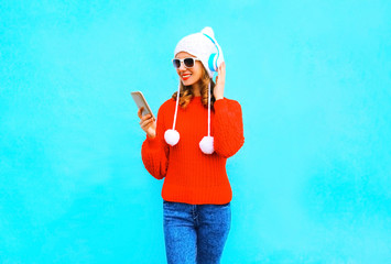 Fashion woman uses smartphone listens to music in wireless headphones in red sweater on blue background