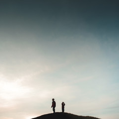Low angle view of brothers standing on hill against sky during dusk