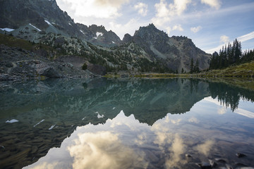 Tranquil view of lake by mountains against cloudy sky at Olympic National Park