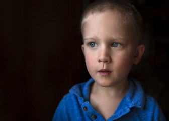 Thoughtful boy looking away against black background