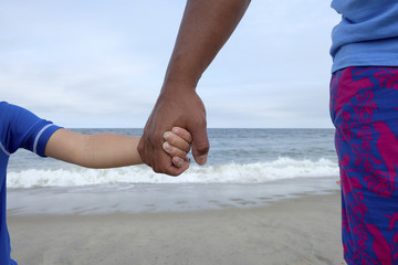 Cropped image of father and son holding hands against sea at beach