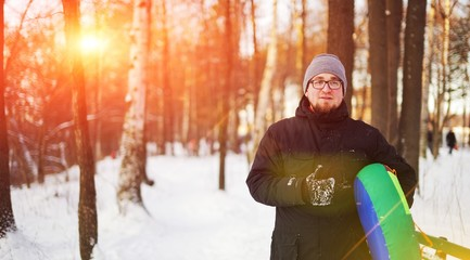 A young bearded guy in glasses goes with the tubing in the winter woods.