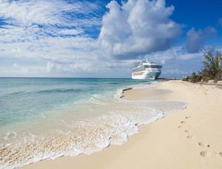 A cruise ship docks in Grand Turk with waves and sand in the foreground.