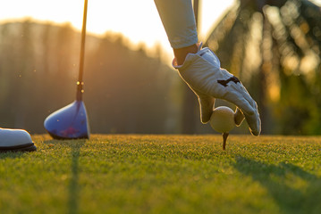 Fotobehang Golf Hand asian woman putting golf ball on tee with club in golf course on evening and sunset time a for healthy sport. Lifestyle Concept.
