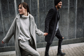 Beautiful couple in stylish clothes in gray tones, city Wall mural