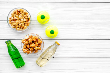 Snacks for watching sport matches and games on TV. Popcorn, rusks near drink and ball on white wooden background top view copyspace