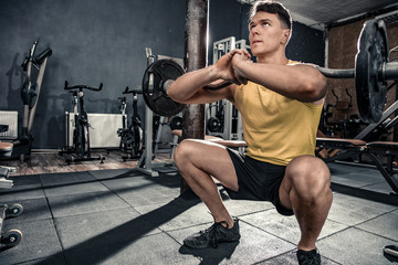 Healthy young man with curl bar performs squats. Photos taken on an atmospheric old gym in a vintage atmosphere