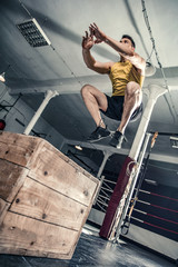 Athletic man performs exercises strengthening his legs. Photos taken on an atmospheric old gym in a vintage atmosphere