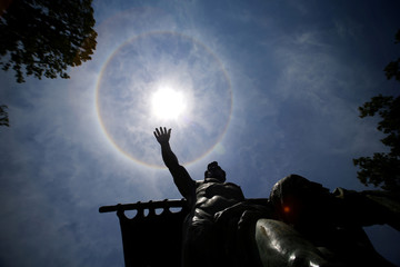 A statue is seen under a solar halo in Santiago