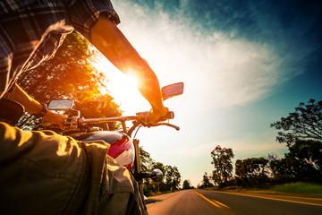 Biker rides motorcycle on an empty asphalt road