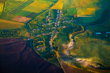 Aerial view of a small russian village with river and green fields during sunrise